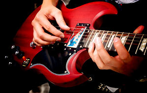 electric guitar close up with fingers playing it